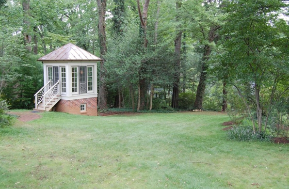 a gazebo at the edge of the woods
